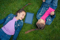 Little girls lying face to face on grass and looking at tablet Royalty Free Stock Image