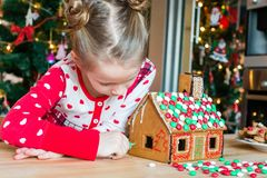 Little girls making Christmas gingerbread house at fireplace in decorated living room. Adorable little girl decorating gingerbread house with glaze background stock photo