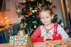 Little girls making Christmas gingerbread house at fireplace in decorated living room. Adorable little girl decorating gingerbread house with glaze background stock photos