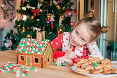 Little girls making Christmas gingerbread house at fireplace in decorated living room. Adorable little girl decorating gingerbread house with glaze background royalty free stock photos