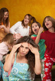 Little Girls Misbehave. Babysitter holds head with wild little girls at a sleepover Stock Photo