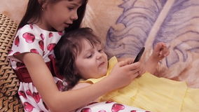 Little girls with mobile. Sisters play with a mobile phone. The children are playing on the couch. Girls in dresses. stock video footage