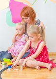 Little girls and mother playing. Royalty Free Stock Photo