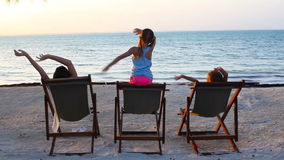 Little girls and mother sitting on beach chairs at sunset. Little girls and young mother sitting on beach chairs at sunset stock video footage