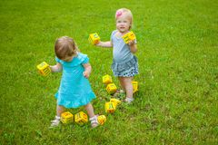 Little girls on nature playing toy Royalty Free Stock Images
