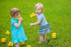 Little girls on nature playing toy Royalty Free Stock Image