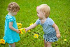 Little girls on nature playing toy Stock Photos