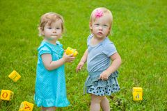 Little girls on nature playing toy Stock Images