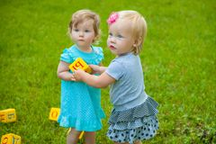 Little girls on nature playing toy Royalty Free Stock Photos