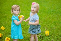 Little girls on nature playing toy Royalty Free Stock Photo