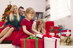 Little girls opening gifts. Portrait of happy family playing during the christmas time Stock Image