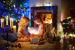 Little girls opening a magical Christmas gift. Adorable little girls opening a magical Christmas gift by a Christmas tree in cozy living room in winter Royalty Free Stock Photo