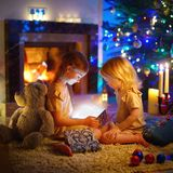 Little girls opening a magical Christmas gift. Adorable little girls opening a magical Christmas gift by a Christmas tree in cozy living room in winter Royalty Free Stock Images