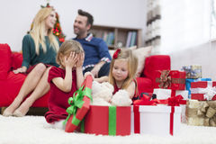 Little girls opening presents. How long I have to wait? Can I see Royalty Free Stock Image