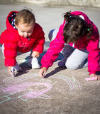 Little girls painting with chalk Royalty Free Stock Image