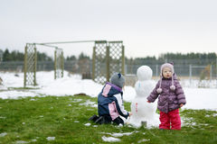 Little girls painting a snowman Stock Images