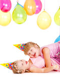 Little girls in party hats playing Royalty Free Stock Image