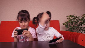 Little girls play with a mobile phone stock video footage