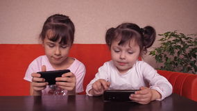 Little girls play with a mobile phone stock footage