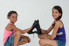 Little girls play with mom's shoes Stock Image