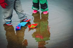 Little girls play with paper boats in spring water. Seasonal activities for kids stock photos