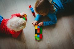 Kids play with plastic blocks, learning concept stock image