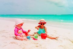 Little girls play with sand on beach Stock Photos