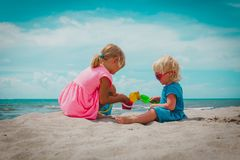 Little girls play with sand on summer beach. Vacation stock image