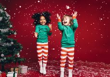 Little girls playing with artificial snow flakes. Little girls in christmas costume having fun and jumping beside a decorated christmas tree. Two kids playing royalty free stock images