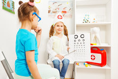Little girls playing a doctor ophthalmologist Royalty Free Stock Photo