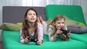 Little girls playing with game pads at home