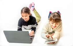 Little girls playing games on the notebook and tablet  Royalty Free Stock Photos