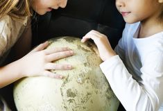 Little girls playing with a globe royalty free stock image