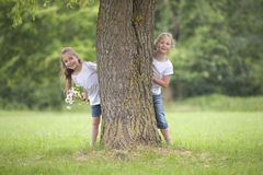 Little girls playing hide and seek Stock Photos