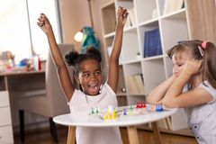 Little girls playing ludo board game. Two little girls sitting in a playroom, playing a ludo board game; one of them just won the game, while the other one is royalty free stock photo
