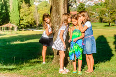 Little girls playing in the park and whispering. Four little girls playing and whispering secrets in the park stock photography