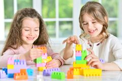 Little girls playing with plastic blocks. Two cute little girls playing with colorful plastic blocks Stock Photo
