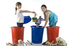 Little girls playing in a plastic drums Stock Images