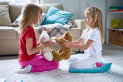 Little Girls Playing with Plush Toys stock photos