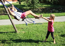Little kids - girls playing on swing. Barefoot little kids - girl in white t-shirt and pink shorts swinging on a swing while playing with second girl standing in Stock Images
