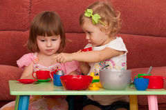 Little girls playing at the table Stock Image