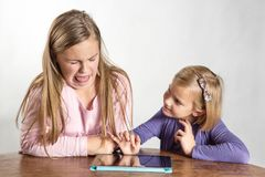 Little girls playing on a tablet computing device Royalty Free Stock Image