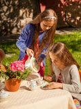 Little girls playing in teatime at yard Stock Photos