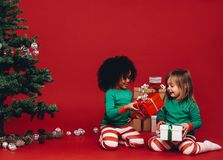 Little girls playing with their christmas gifts boxes stock images