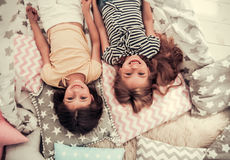 Little girls playing. Top view of two cute little girls looking at camera and smiling while playing together at home Royalty Free Stock Photos