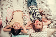 Little girls playing. Top view of two cute little girls looking at camera and smiling while playing together at home Royalty Free Stock Photography