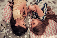 Little girls playing. Top view of two cute little girls looking at each other and smiling while playing together at home Royalty Free Stock Images