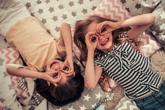 Little girls playing. Top view of two cute little girls making glasses with their hands, looking at camera and smiling while playing together at home Stock Images