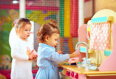Little girls playing at toy kitchen in kindergarten. Cute little girls playing at toy kitchen in kindergarten Stock Photos