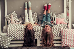 Little girls playing. Two cute little girls are looking at camera and smiling while lying on their backs on bed in children`s room Stock Images